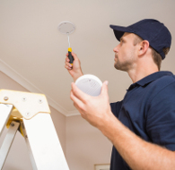 An engineer fitting a smoke alarm to the ceiling